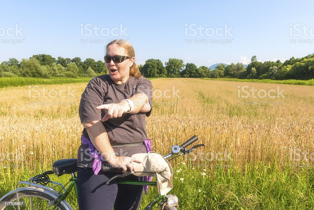 overweight mature woman pointing on bicycle in wheat field royalty-free stock photo