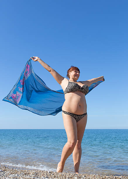 overweight middle aged woman at the sea - older women bikini stock pictures, royalty-free photos & images