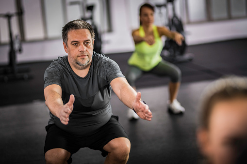 istock Overweight middle-aged man doing squats in aerobics class 1018647962