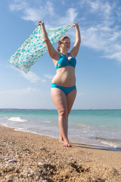 overweight middle-aged woman with pareo walks along seashore - older women bikini stock pictures, royalty-free photos & images