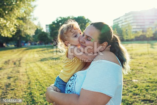 Modern real parents with body positive attitude, tattoos, piercings and positive lifestyle, spending afternoon with their kids in the park.