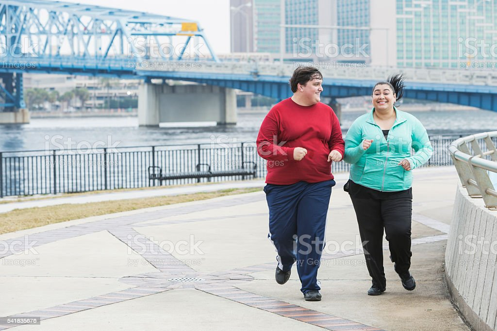 Overweight people exercising, running and smiling stock photo