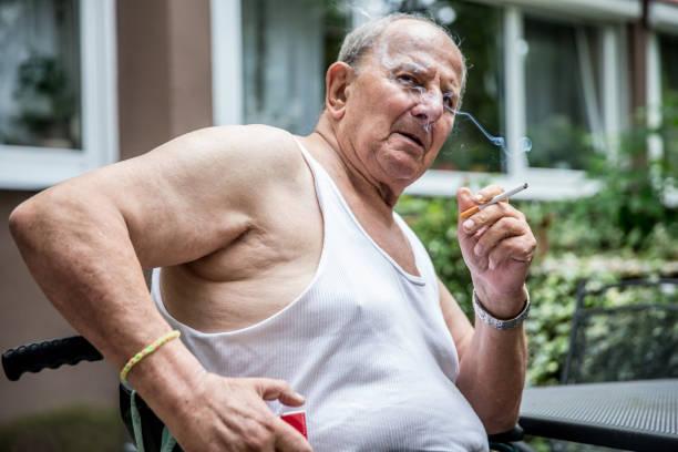 Hombre mayor sobrepeso fumar cigarrillo - foto de stock