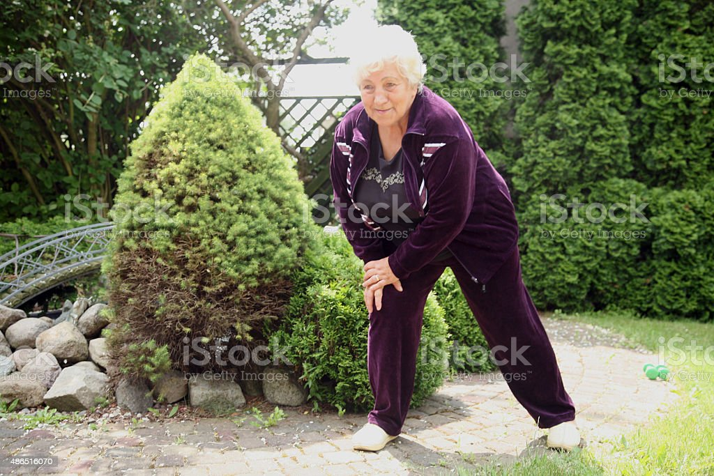 70 years old overweight woman exercising outdoors.
