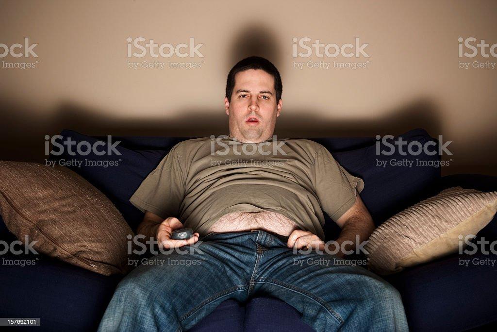 Overweight slob watching TV stock photo