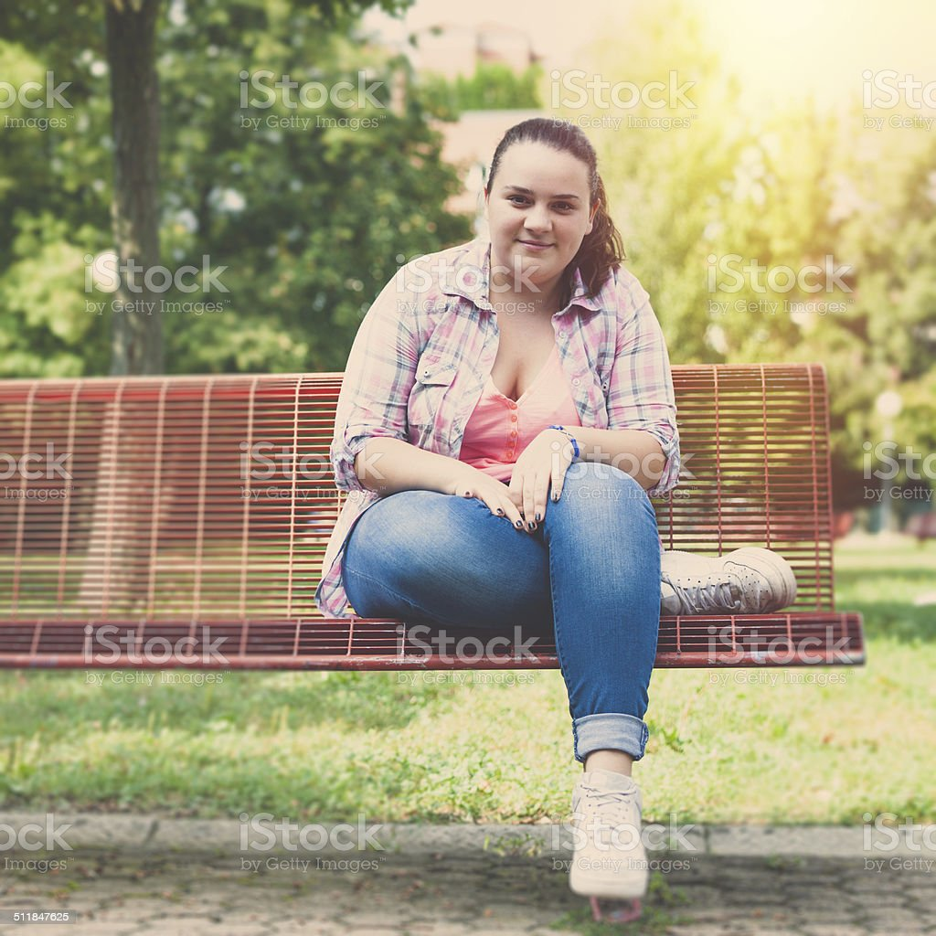 Overweight serene teenage girl sitting on a bench in the park.