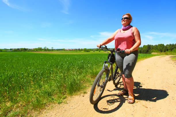 Übergewicht Frau und Fahrrad. Aktive Menschen, die Sommerferien auf dem Land genießen. – Foto