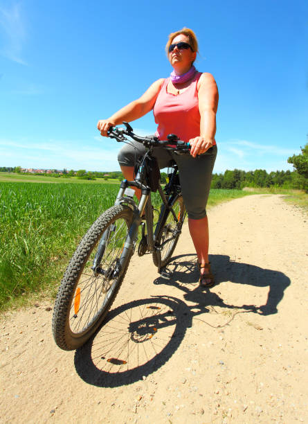 Overweight woman and bicycle. Active people enjoying summer holidays on countryside. Overweight woman and bicycle. Active people enjoying summer holidays on countryside. fat biker stock pictures, royalty-free photos & images