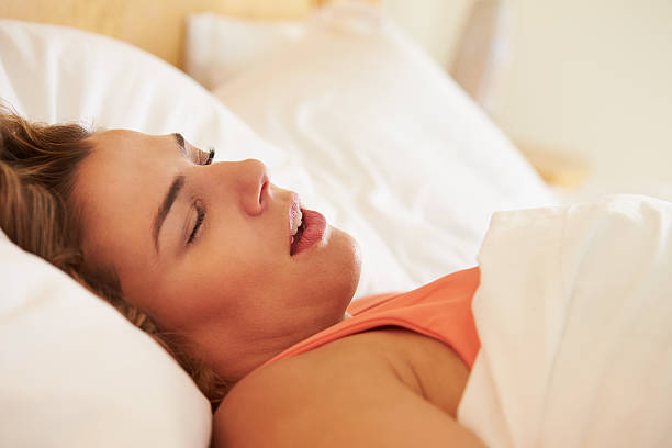 Overweight Woman Asleep In Bed Snoring Close Up Of Overweight Woman Asleep In Bed Snoring On Her Own mouth open stock pictures, royalty-free photos & images