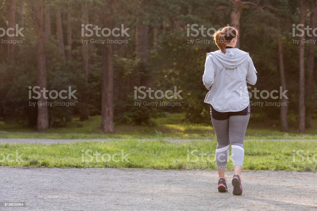 Overweight woman back running. Weight loss concept stock photo