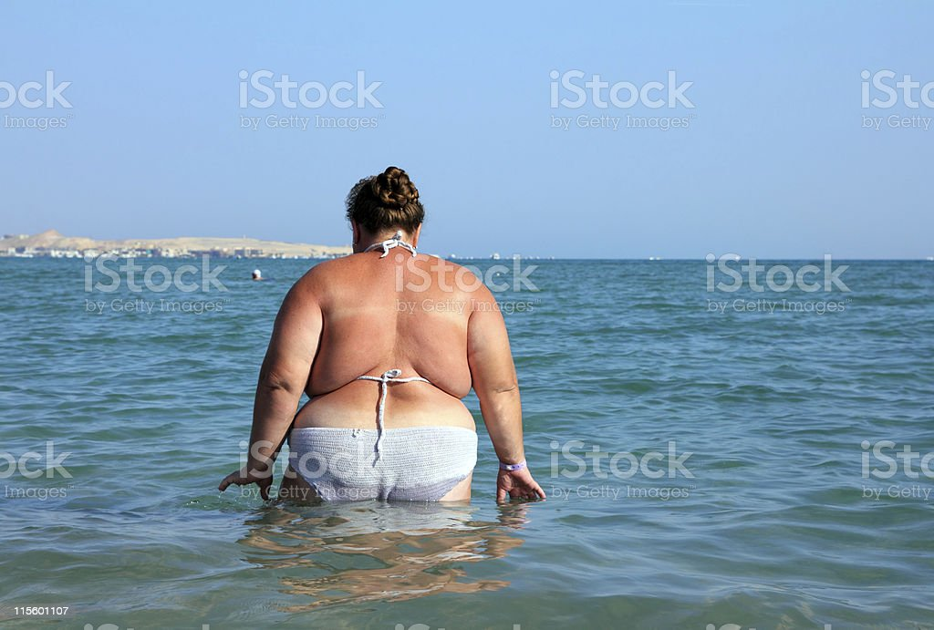 overweight woman bath in sea stock photo