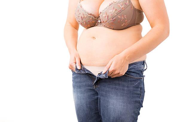 overweight woman can't close her jeans - damen hosen für mollige stock-fotos und bilder