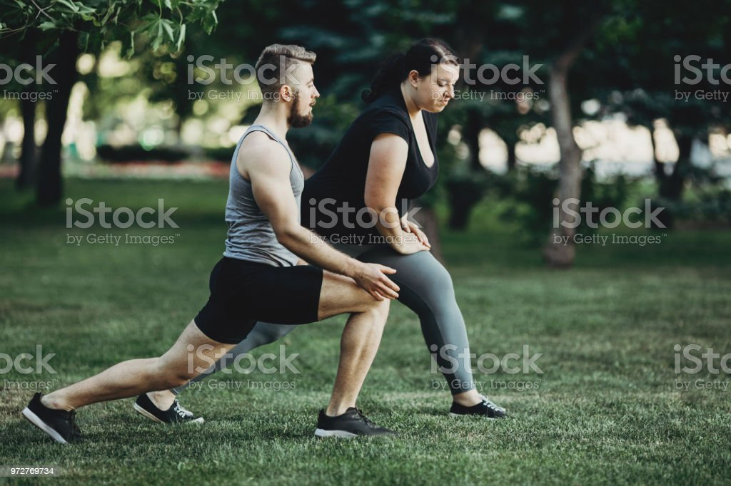 Overweight woman doing lunges exercise with trainer support. Personal...