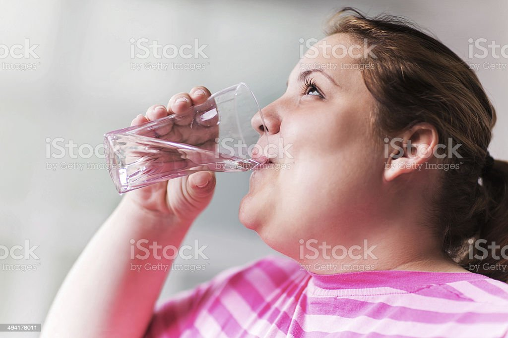 Overweight woman drinking water. stock photo