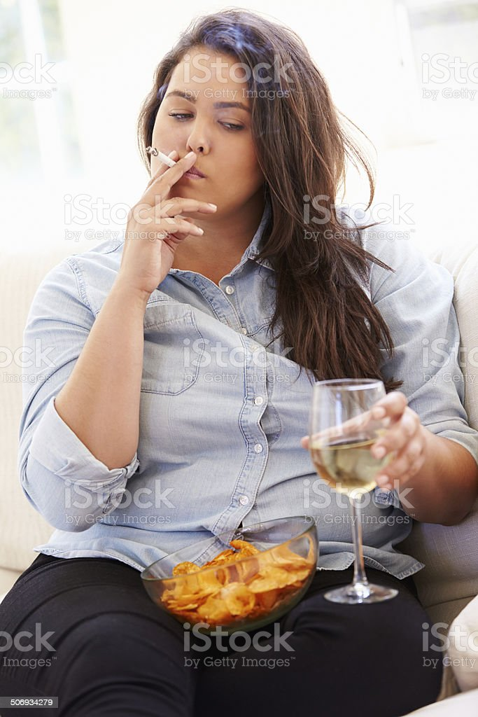 Overweight Woman Eating Chips, Drinking Wine And Smoking stock photo