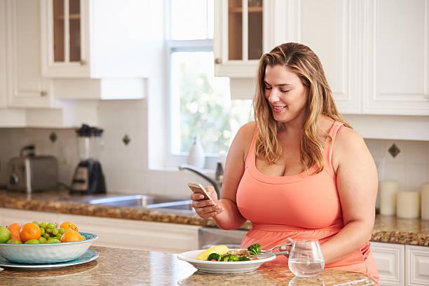übergewichtige frau essen gesunde mahlzeit und mit handy - fett nährstoff stock-fotos und bilder
