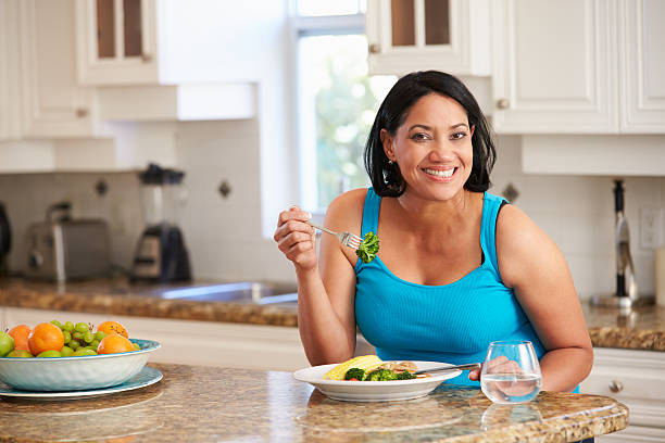 overweight woman eating healthy meal in kitchen - fat nutrient stock photos and pictures