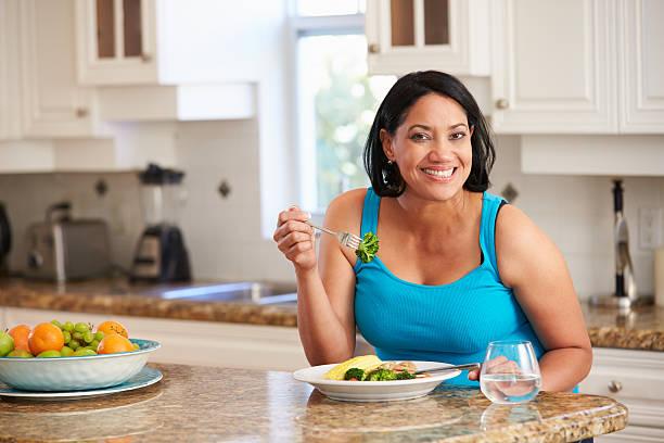 übergewichtige frau essen gesunde mahlzeit in der küche - fett nährstoff stock-fotos und bilder