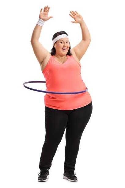 übergewichtige frau, die das training mit einem hula-hoop - hula hoop workout stock-fotos und bilder