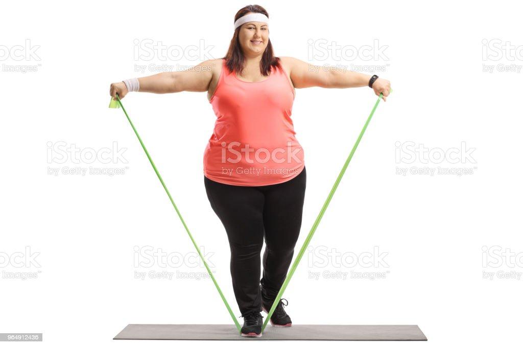 超重婦女在墊子上用橡皮筋運動 - 免版稅20多歲圖庫照片