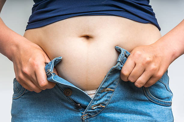 overweight woman getting dressed wearing jeans - enganliegende jeans outfits stock-fotos und bilder