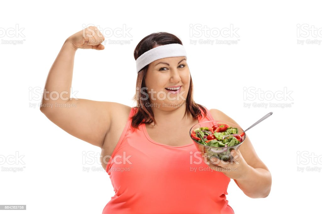 Overweight woman holding a salad and flexing her bicep royalty-free stock photo