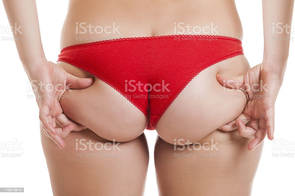 Overweight woman holding and pinching fat body bottom or buttocks stock photo