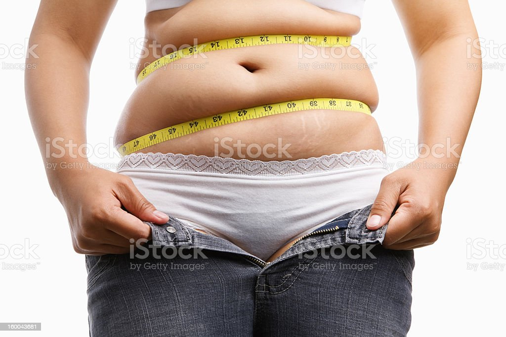 Overweight woman holding her unzip jeans stock photo