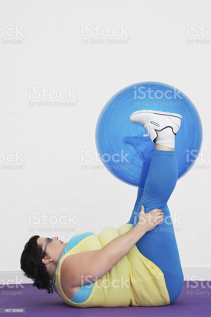 Overweight Woman Holding up Exercise Ball With Legs royalty-free stock photo