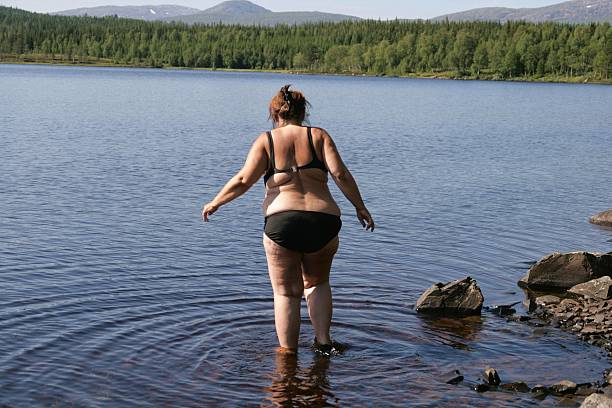 overweight woman in bikini - older women bikini stock pictures, royalty-free photos & images