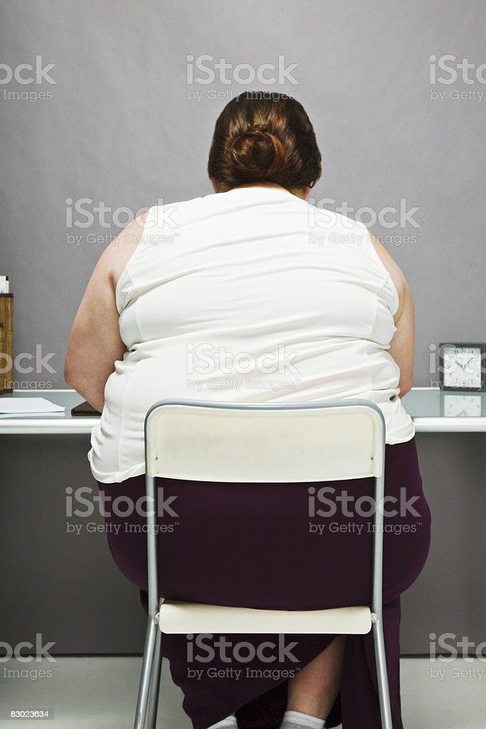 Overweight woman in chair, back view royaltyfri bildbanksbilder