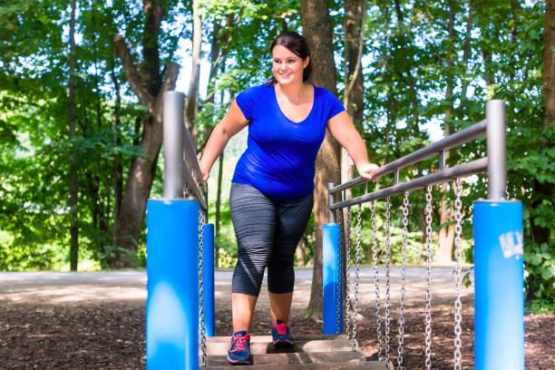 übergewichtige frau im kletterpark sport treiben - damen sporthose übergröße stock-fotos und bilder
