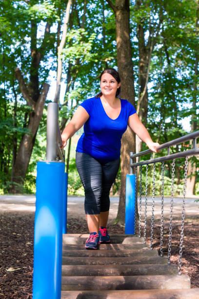 übergewichtige frau im kletterpark sport treiben - damen leggings übergrößen stock-fotos und bilder