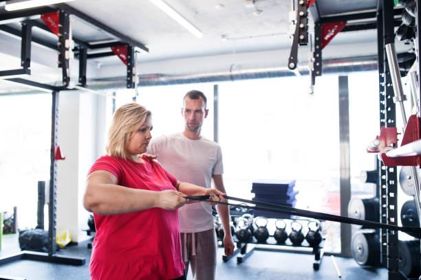 mujer con sobrepeso en brazos de gimnasio entrenamiento con trx fitness tiras. - hombres grandes musculosos fotografías e imágenes de stock