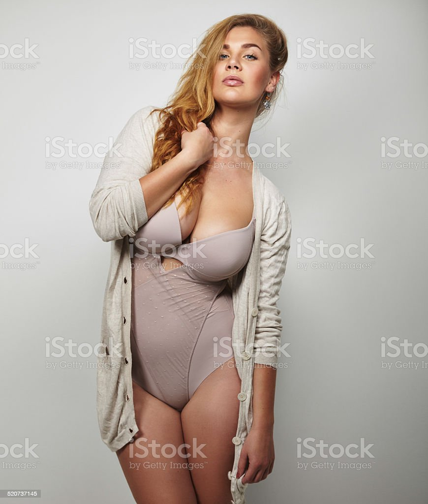 Overweight woman in underwear posing confidently stock photo