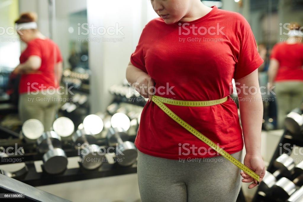 Overweight Woman Measuring Waist in Gym stock photo