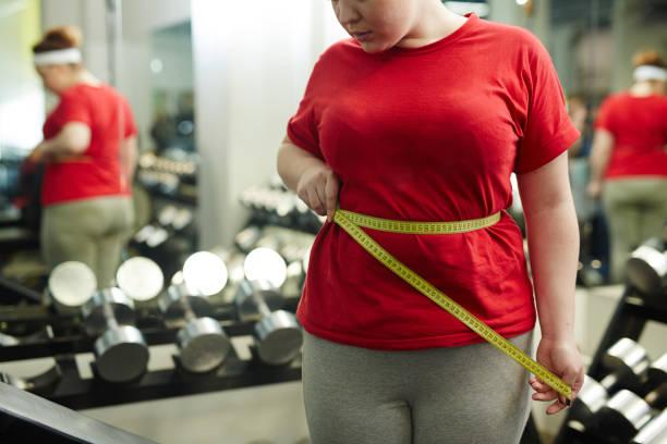 overweight woman measuring waist in gym - taillentrainer stock-fotos und bilder