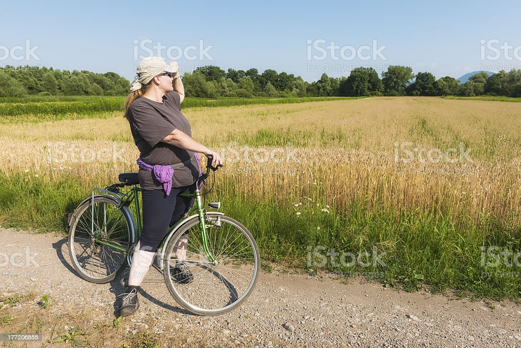 Overweight woman on bike royalty-free stock photo