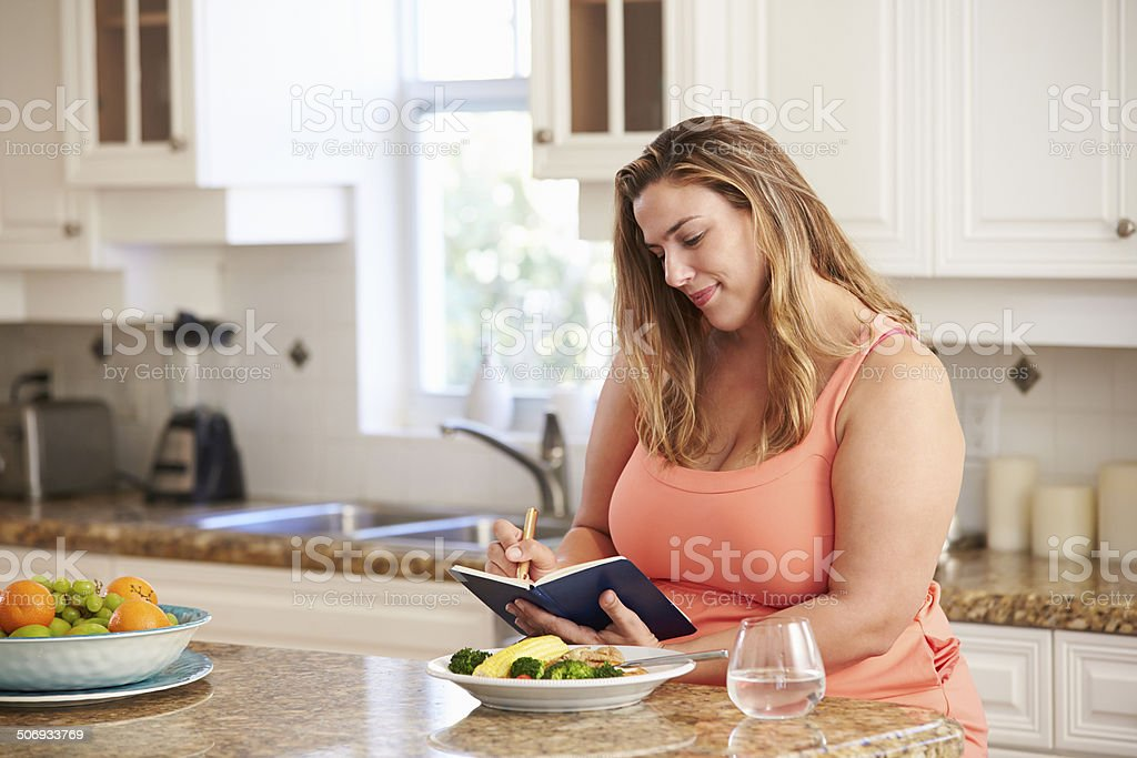 Overweight Woman On Diet Keeping Food Journal stock photo
