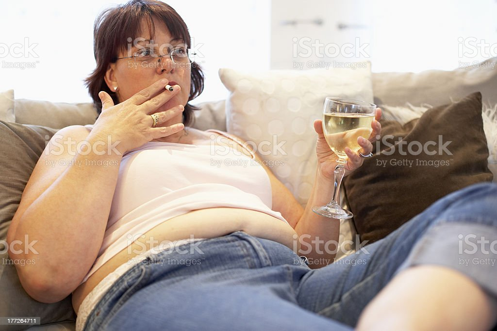 Overweight Woman Relaxing On Sofa stock photo