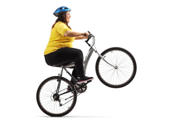 Overweight woman riding a bike and doing a wheelie Overweight woman riding a bike and doing a wheelie isolated on white background fat biker stock pictures, royalty-free photos & images
