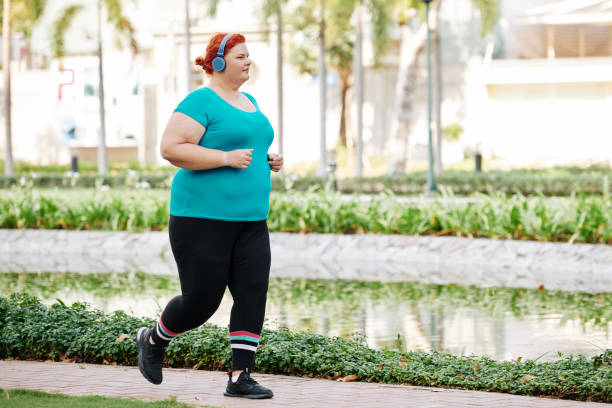 Overweight woman running in park stock photo