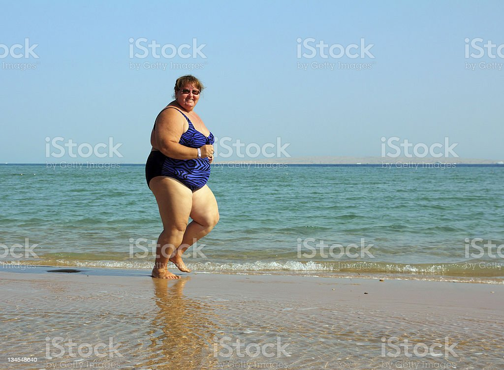 overweight woman running on beach stock photo