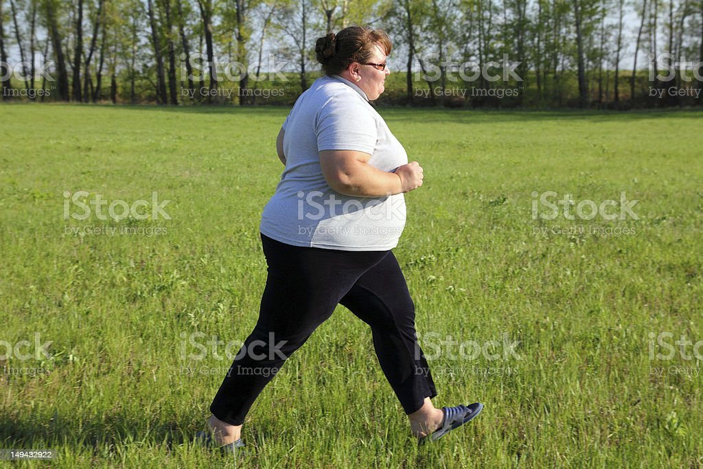 overweight woman running on meadow royalty-free stock photo