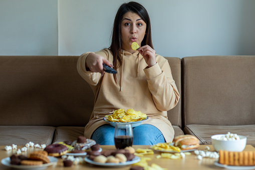 Overweight woman sit on the sofa with junk food
