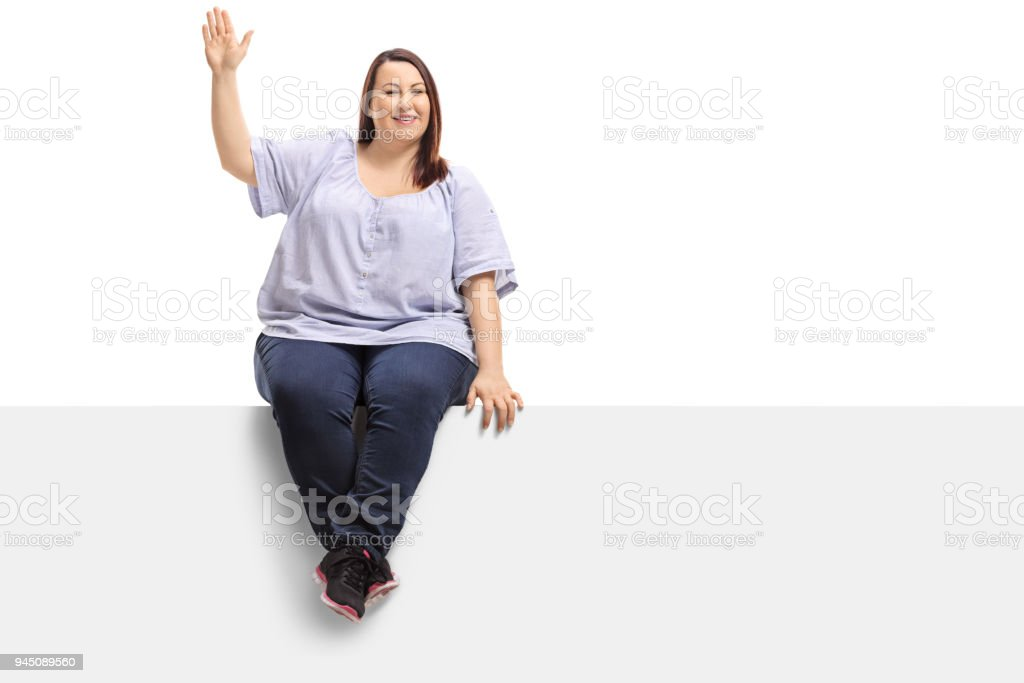 Overweight woman sitting on a panel and waving at the camera stock photo