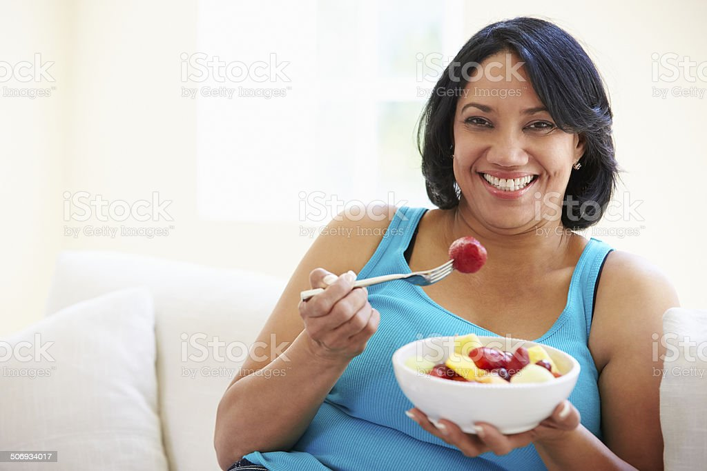 Overweight Woman Sitting On Sofa Eating Bowl Of Fresh Fruit stock photo