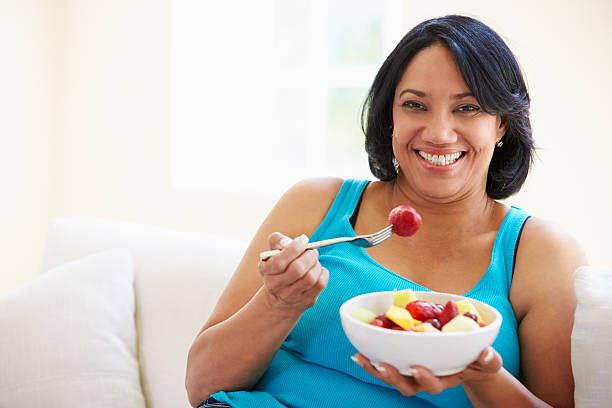 overweight woman sitting on sofa eating bowl of fresh fruit - fat nutrient stock photos and pictures