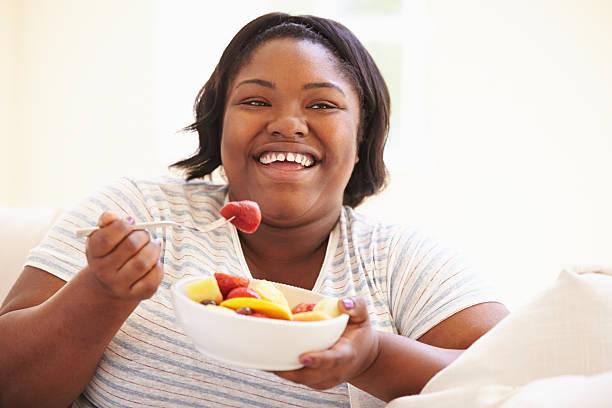 übergewichtige frau sitzt auf sofa, essen schale mit frischem obst. - fett nährstoff stock-fotos und bilder