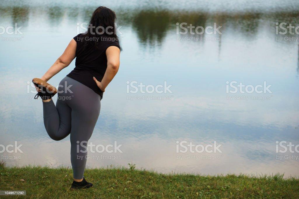 Overweight woman stretching legs before running stock photo